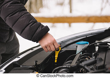Man checking oil level in his car using dipstick - Car...