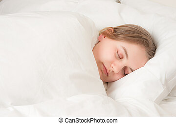young woman asleep in bed - a pretty young woman asleep in...