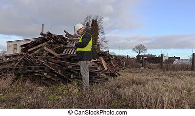 Engineer using tablet and walking near wooden pallets
