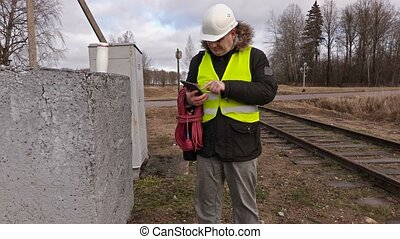 Railway electrician use tablet near railway
