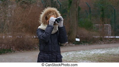 Young beautiful female girl photographer taking photos with camera