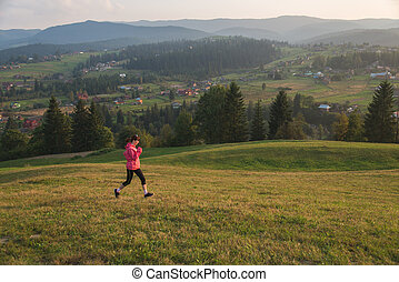 Girl runs along the mountain terrain