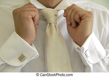 male hands with cuff links in shirt holding white collar