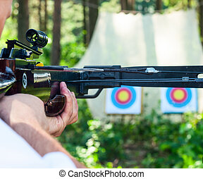 Man aiming crossbow at target outdoor