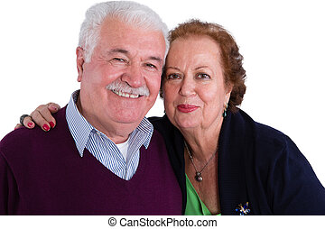 Happy loving senior couple posing in a close embrace smiling...