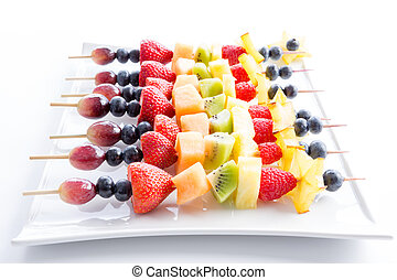 Serving of colorful fresh fruit kebabs - Serving of colorful...