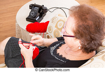 Grandma sitting knitting near the phone - Grandma sitting...