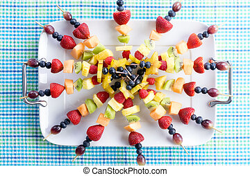 Healthy fresh fruit kebabs on a picnic table