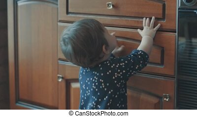 Little baby standing near the cupboard, then sit down on the...