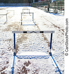 Empty snowy running track with hurdles - Empty running track...