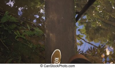 Legs man walking on a wooden bridge, view from above. -...