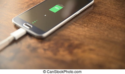 4K Motion view of charging smartphone on wooden table.