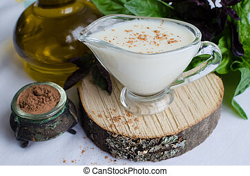 Classic European white sauce Bechamel in saucer with nutmeg,...