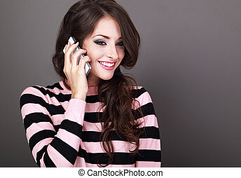 Beautiful makeup happy woman talking on mobile phone on grey...