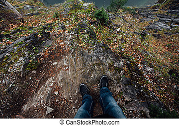 man stands at the edge of the picturesque cliff. Tourist in jeans