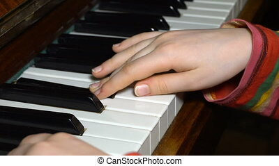 kid hands playing on a piano key