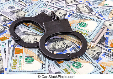 Police steel handcuffs lying on the heap of american dollars