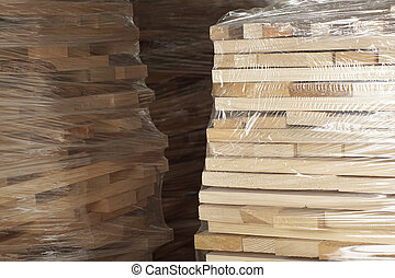 Wooden planks stacked in rows wrapped in plastic foil