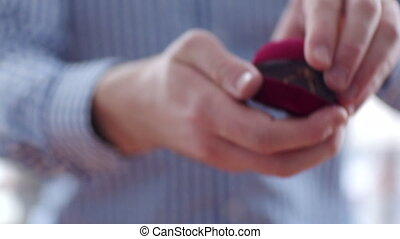 Man holding gift box with engagement ring in his hands