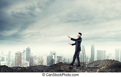 Young businessman in blindfold walking carefully and...