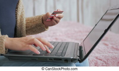 Woman shopping online at laptop with credit card - Close up...