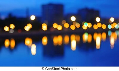 City waterfront in night time with lights of buildings and street lamps. Blurred view of city embankment
