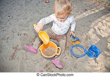 Sandpit - Cute Caucasian baby girl playing with the sand in...