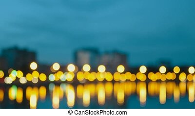 Blurred view of city embankment. City waterfront in night time with lights of buildings and street lamps