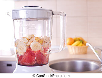 Blender with fruits in bowl