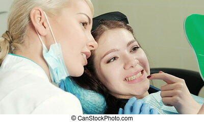Healthy white woman teeth and dentist mouth mirror closeup....
