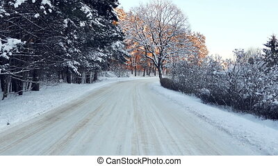 Smooth ride down the snowy forest road in cold winter....