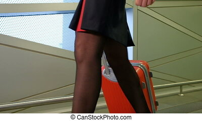 Stewardess walks down hallway at airport terminal waiting...