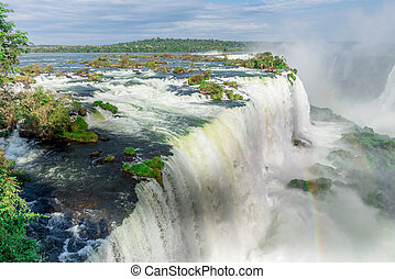 The Iguazu Falls with clouds and blue sky on the background...