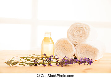 Towels lavender and masage oil on a table in spa salon
