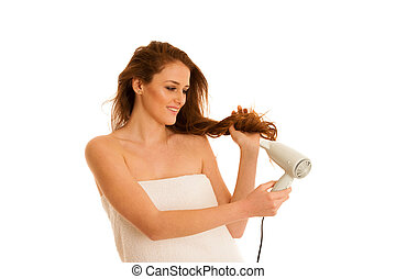 beautiful young woman dries hair  with a blow dryer