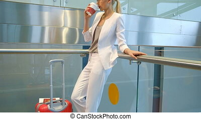 Shooting from down blonde woman standing drinking coffee in airport