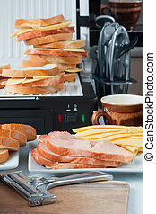 Hot cheese and ham sandwiches, a slicer, cup of coffee...
