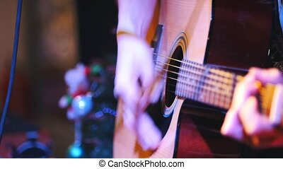 Guitarist holds acoustic guitar near microphone at concert...