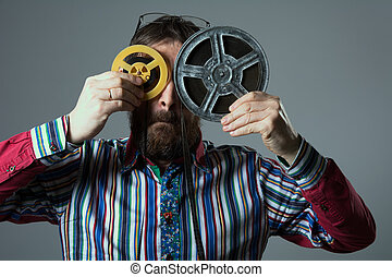 Bearded man with two 16mm film reel. A man in a striped...