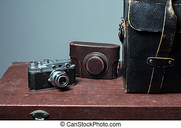 Camera and carrying case on old suitcase. Background...