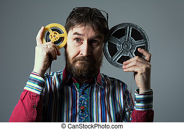 Bearded man with two film reel. A man in a striped shirt...