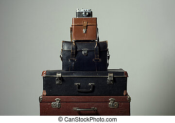 Stack of old shabby suitcases and camera. Concept traveler...