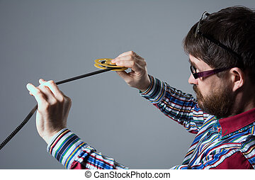 Bearded man looks at 8mm film. A man in a shirt Glasses...