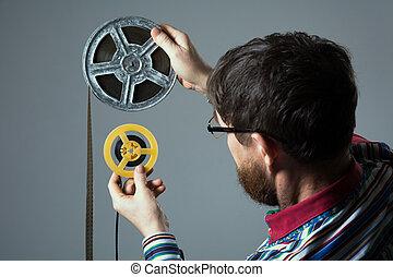 Bearded man watch two film reel 16mm. A man in a striped...