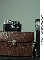 Close-up of a stack vintage shabby suitcases and camera -...