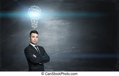 Businessman on black chalkboard background with a glowing gridshell bulb above him.