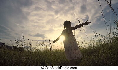 One little girl dancing in the field at the sunset time. Kid...
