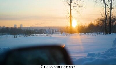 The car rides on winter road at sunset. Point of view
