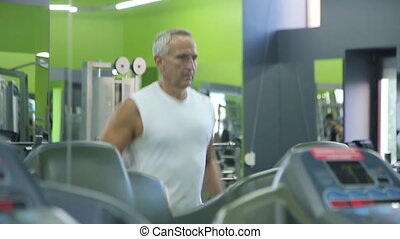 Old man runs on a treadmill. Full HD