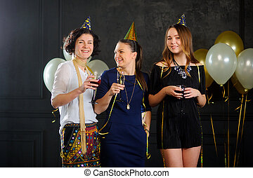 Three young women celebrate someone's birthday. In hands at...